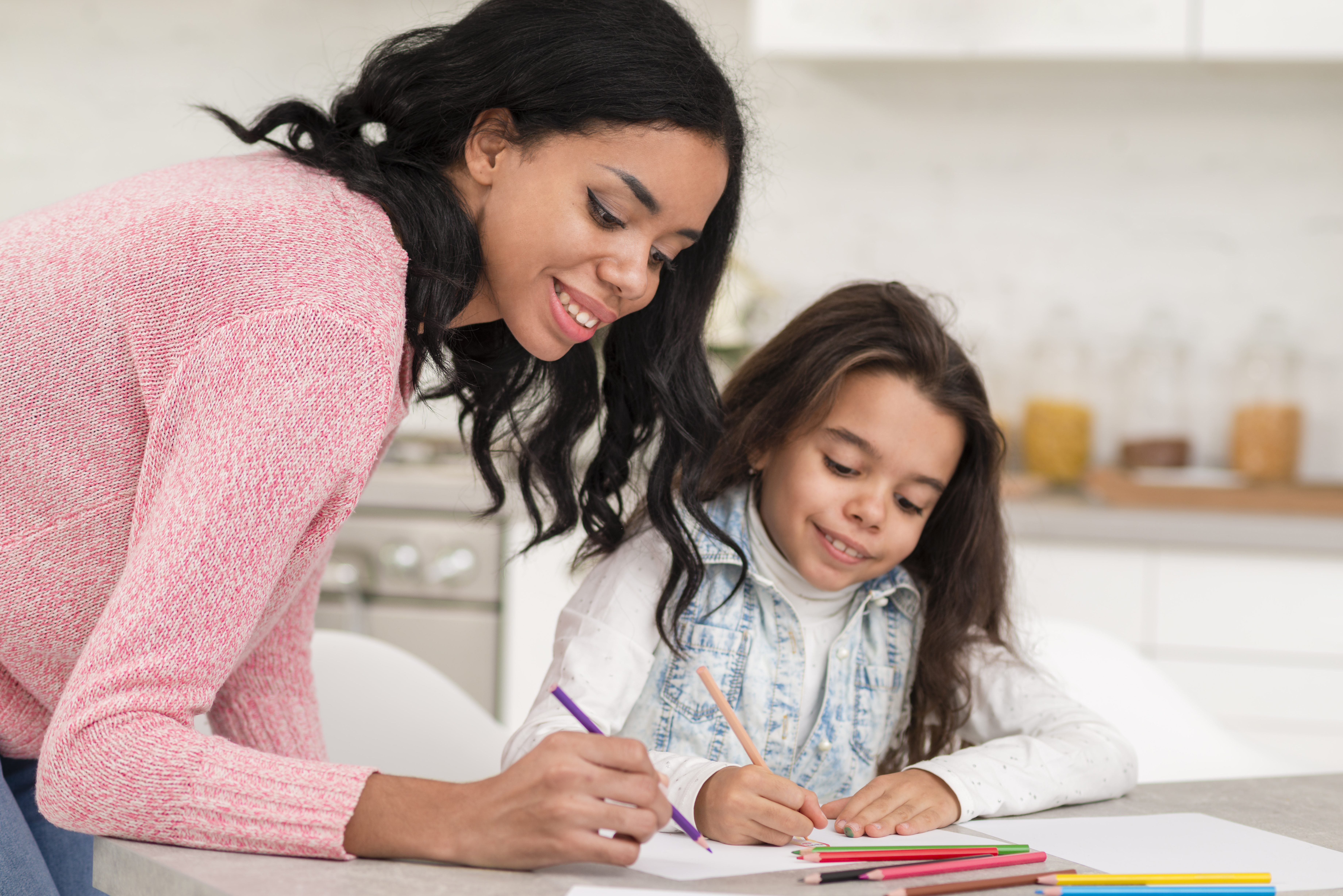 mother helping daughter to color with colored pencils