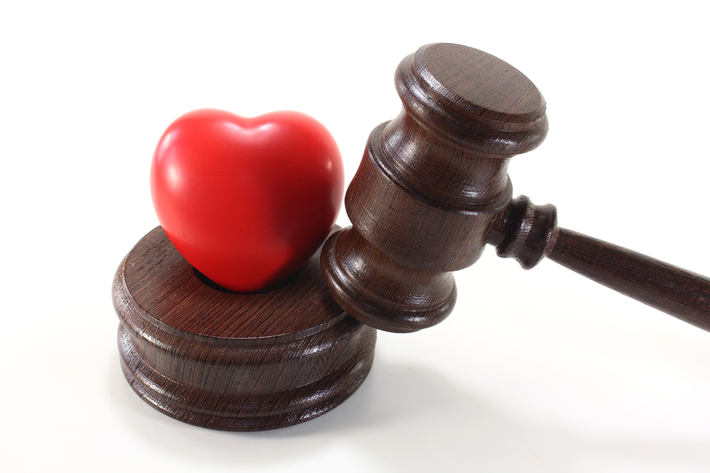 Judge's gavel and a small red heart against a white background.
