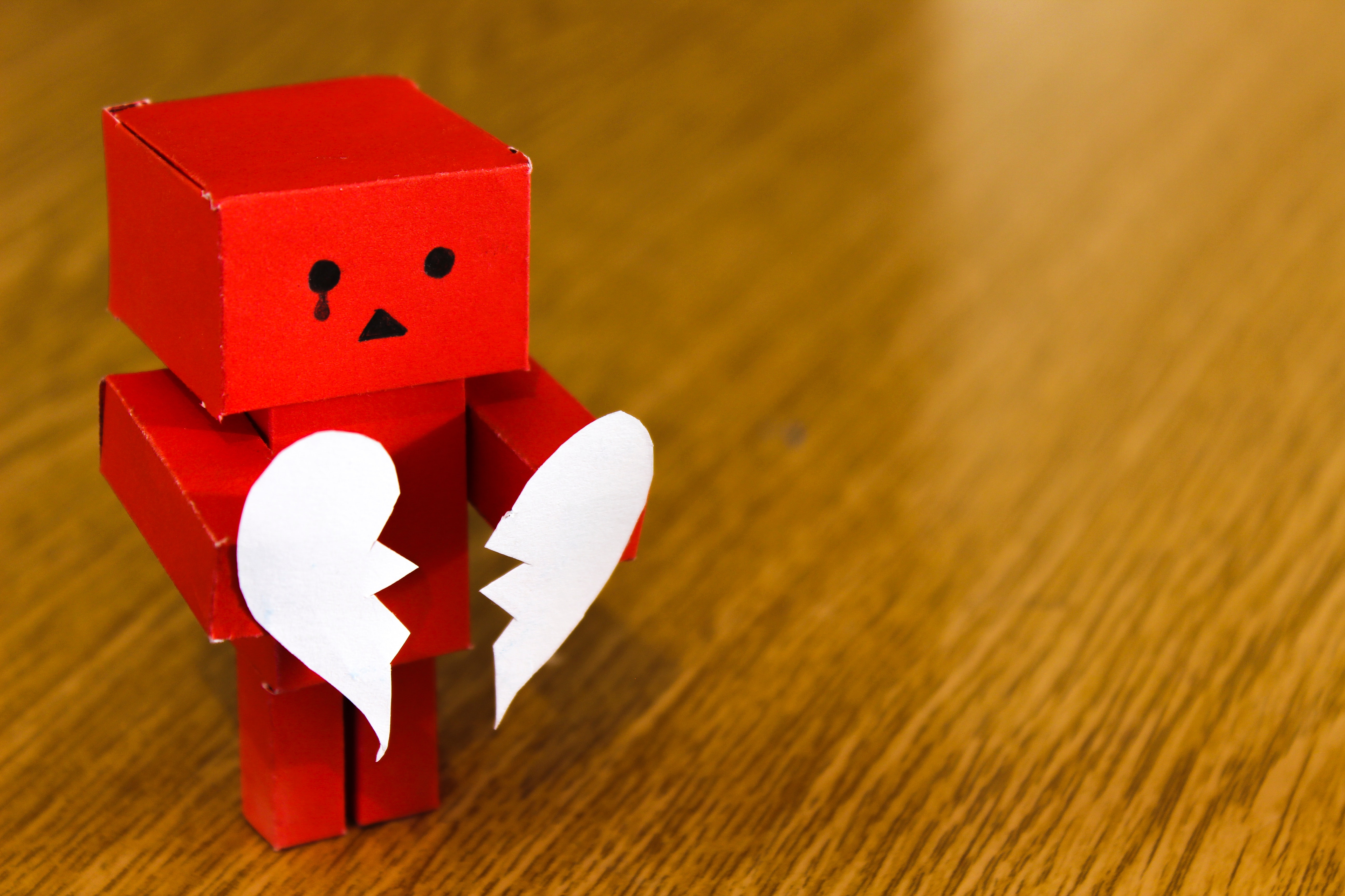 A crying robot made of paper holding a broken heart.